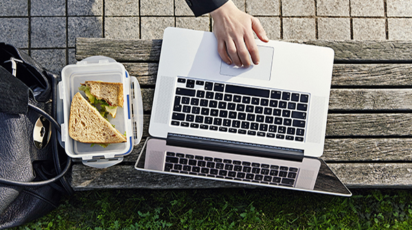 woman eating lunch and working in park.
